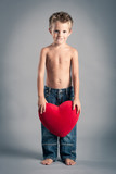 Little boy playing with red heart. Valentines Day concept.