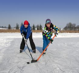 Zwei Jungen spielen Eishockey auf zugefrorenem See