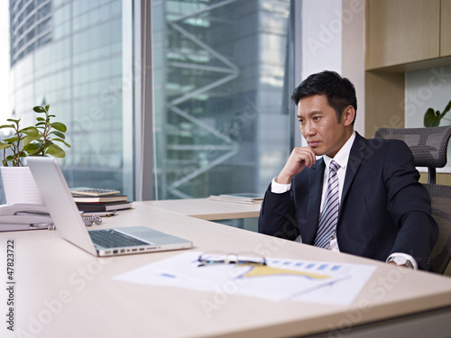 asian businessman thinking in office