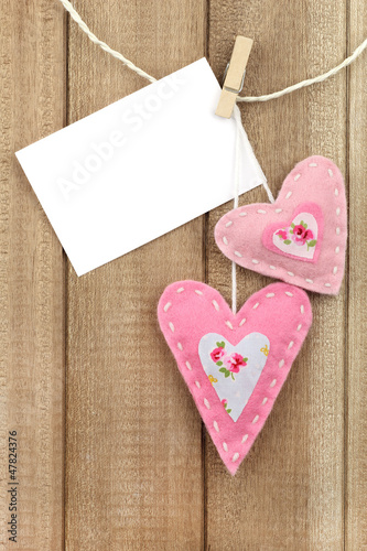 Two hearts hanging on line with a message attached with a peg