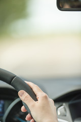Hand of woman on steering wheel inside car