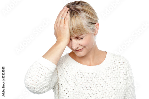 Sad middle aged woman suffering from headache