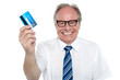 Cheerful aged employer holding up a cash card