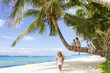 three children - boy and girls - sitting on palm tree on tropica
