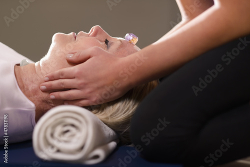 Young therapist arranging crystals on female client for reiki th