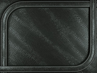 Black mock croc or alligator skin background with stitched patte