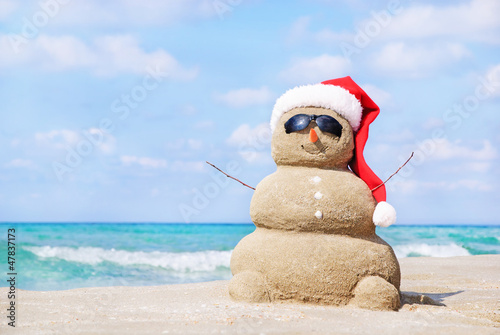 Tuinposter Ontspanning Smiling sandy snowman in red santa hat on the sea beach.