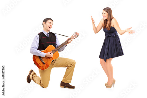 A male playing on a guitar and singing to his girlfriend