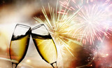 champagne glasses against  fireworks