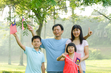 asian family during independence day, holding malaysian flags