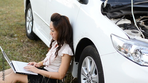 Female Driver on notebook and car breakdown