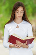 teenage girl dressed in white reading red book