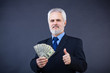 business man holding cash and showing thumbs up