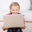lächelndes mädchen schaut auf laptop