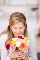 frau riecht an einem strauß rosen