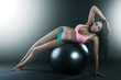Pretty young woman laying on fit ball, doing workout