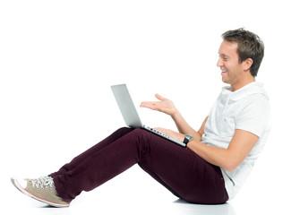 junger mann schaut lachend auf sein laptop