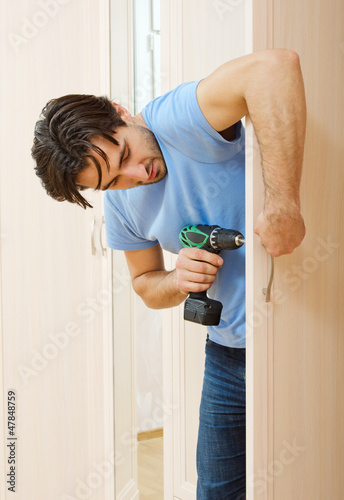 man repairing the door handle furniture