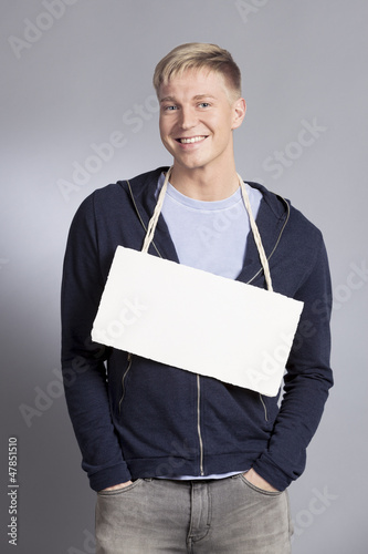 Smiling friendly man holding blank signboard.