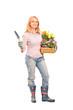 Female gardener holding flowers and gardening equipment