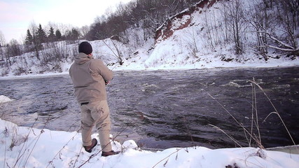 Man fishing trout in forest river