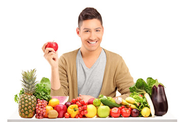 Handsome guy holding an apple on a table full of various food