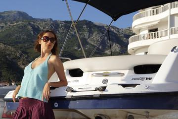 Young beautiful girl near the yacht