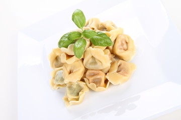 Tortellini on a plate decorated with fresh basil