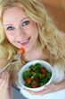 Beautiful blond woman eating fresh salad