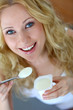 Beautiful blond woman eating yoghurt