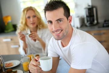 Portrait of young man holding cup of coffee