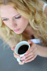 Upper view of blond woman drinking coffee