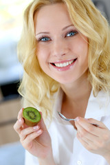 Portrait of beautiful girl eating kiwi
