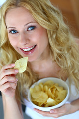 Smiling woman eating potato chips