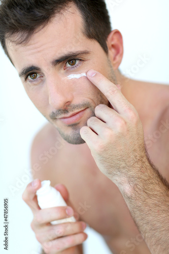 Handsome guy applying concealer around his eyes