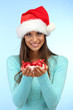 beautiful young woman holding snow with christmas balls,