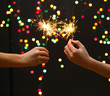 beautiful sparklers in woman hands on garland background.