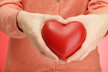 Red heart in woman hands, on red background
