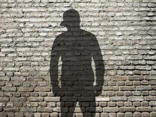 ombre de jeune à casquette sur vieux mur