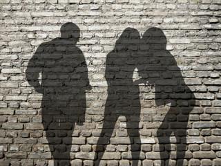 ombres 1 homme 2 femmes sur mur de briques