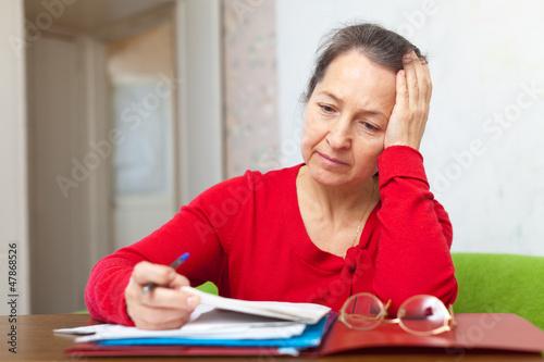 Sad mature woman reads documents
