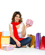 Young girl in red scarf sitting with shopping bags isolated on w