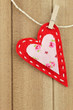Red handmade felt heart clipped with clothespin on wood