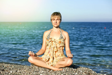 woman near the sea in the lotus position;