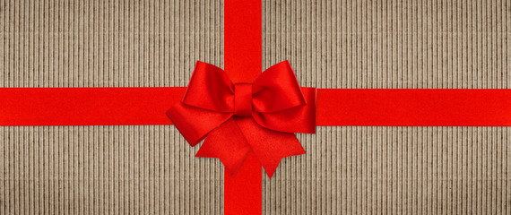 red ribbon bow on recycled cardboard paper background