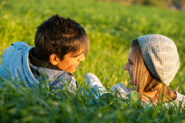 Couple laying in grass field at sunset.