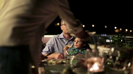 Family with friends eating dinner in the evening, steadicam shot