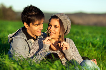 Girl showing flower to boyfriend outdoors.