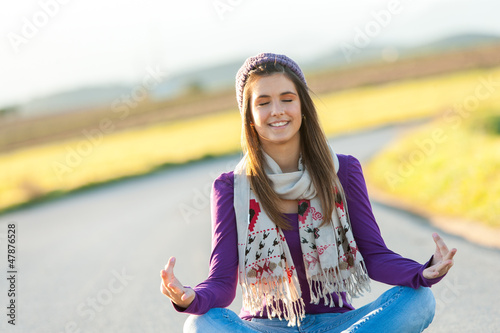 Cute girl meditating in countryside.