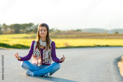 Young girl meditating outdoors.